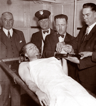 FBI agents display the lifeless body of Floyd after he was killed in a shootout Oct. 22, 1934. One controversial account claims Floyd was murdered by FBI agents as he lay wounded and disarmed.